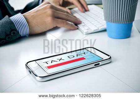 closeup of a young caucasian man sitting at his office desk where there is a smartphone with the text tax day in its screen