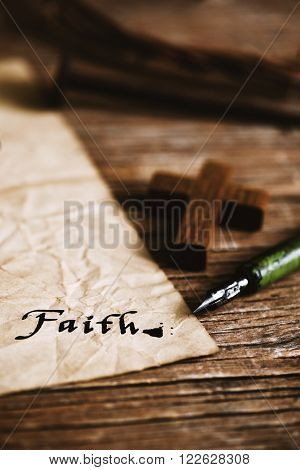 closeup of a small wooden christian cross, an old dip pen and a yellowish paper with the word faith written with black ink in it, on a rustic wooden table