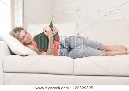 young beautiful caucasian woman reading book or studying lying comfortable on home couch or sofa looking happy and relaxed in culture concept and lifestyle