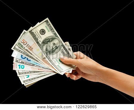 Woman's hand is giving euro and dollars money isolated on black background