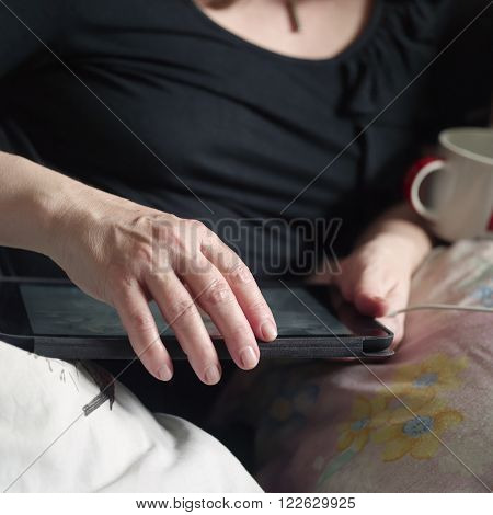 Female hands working or playing on a tablet while lying in a bed concept of leisure and free time