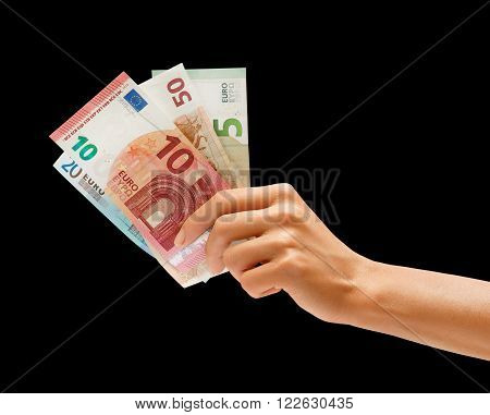Woman's hand holding euro money isolated on black background