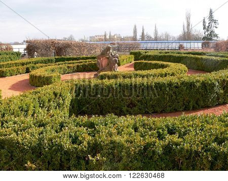 Green bushes labyrinth, hedge maze in the Czech Republic.In the background statue