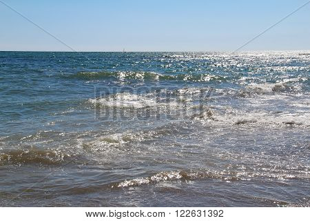 Sunny patches of light on a clean sea water and blue sky. Italy.
