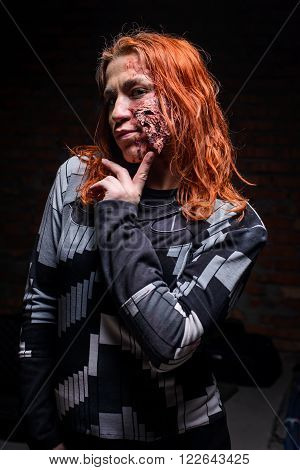 KIEV,UKRAINE - February 20 : portrait of girl in the role of a zombie with a scary make-up coquettish and seductive looking at the camera during the quest game in zombie theme in Kiev,Ukraine on February 20,2016.