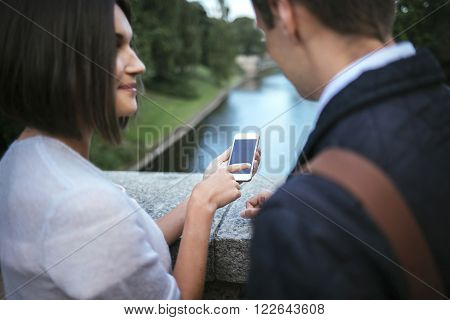 Youn couple using smartphone outdoors tap on screen