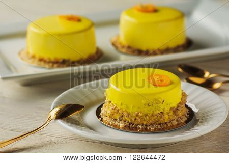 Mini Mousse Cakes Covered With Yellow Glaze. Modern European Cake On Light Wooden Background.