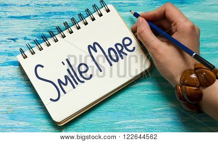 Smile more. Inspirational quote handwritten ink and brush custom lettering for posters t-shirts and cards. writing a note with a fountain pen on a notebook. Handwritten text happiness concept