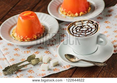 Mini Orande Mousse Cakes Covered With Glaze And Coffee. Modern European Cake On Light Wooden