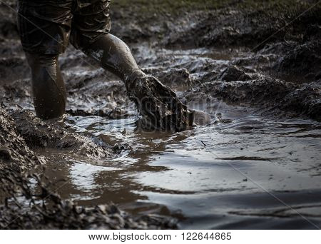 Deep muddy water with feet splashing through and dragging the mud in a race