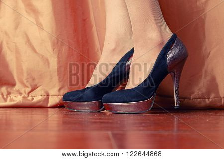 Low angle view of women in fashionable high heel shoes on wooden floor