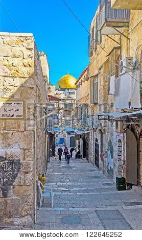 JERUSALEM ISRAEL - FEBRUARY 16 2016: The narrow street leads to the Temple Mount and boasts the view on the golden cupola of the Dome of the Rock on February 16 in Jerusalem.
