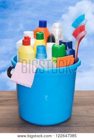Detergents in color bottles brush and napkins in a bucket on a wooden table against the sky.