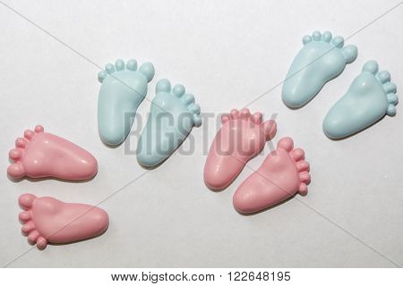 Small, pink and blue baby feet decorations in pairs