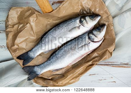 Two Raw Sea Bass on paper and white rustic background