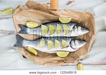 Two Raw Sea Basses on paper and white rustic background