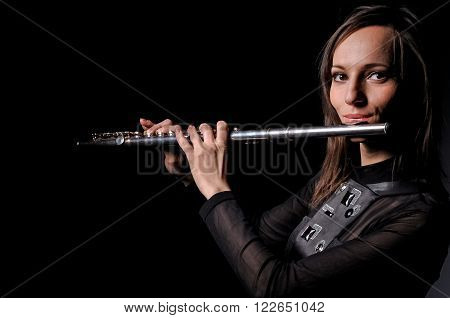 Young elegant woman girl flutist performer playing flute musical instrument on black.