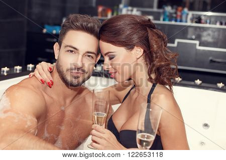 Happy couple with glasses of champagne in jacuzzi honeymoon