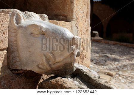 AYIA NAPA, CYPRUS - MARCH 13, 2016: Ancient fountain in the form of lion's head in the Ayia Napa monastery. Present buildings erected in 15th century, and is the main landmark of the village