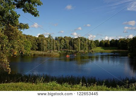 ORANIENBAUM, RUSSIA - AUGUST 29, 2015: People ride pedal boats on the Lower Pond of Oranienbaum palace. Founded in 1710-1727, it is listed as UNESCO World Heritage site