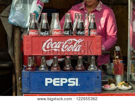 Phnom Penh Cambodia- January 02 2014. Coca-Cola and Pepsi bottles stacked in plastic container - vintage style. Symbolic representation of one of the greatest business rivalries of all time.