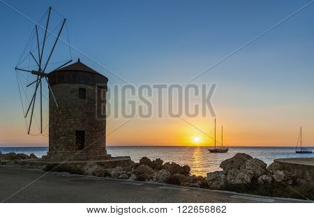 Mill on the background of the rising sun in the harbor of Mandraki. Rhodes Island. Greece