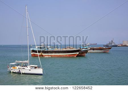 GULF OF ADEN, DJIBOUT - FEBRUARY 08, 2016: Luxury sailing boat, fishing and cargo ships at anchor in the port of Djibouti