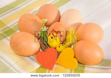 Brown eggs with easter decoration and two felt hearts on checkered cotton napkin.