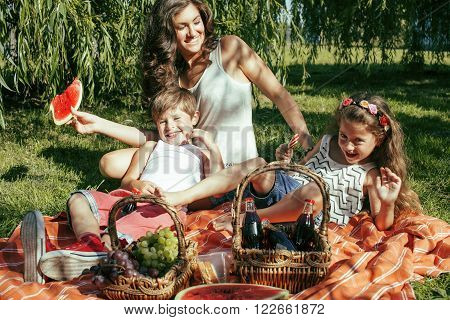 cute happy family on picnic laying on green grass mother and kids, warm summer vacations close up, brother and sister together