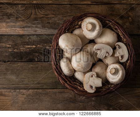 Fresh raw porcini boletus mushrooms in round wooden bowl. Wood background.