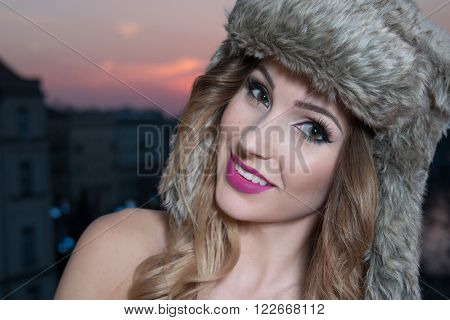 portrait of beautyful bruntete woman wearing fur hat during the sunset