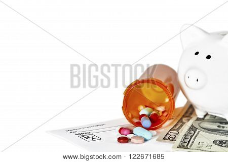 Bottle of prescription medications laying on top of a one hundred dollar bill and a prescription form and piggy bank in background with shallow depth of field isolated on white