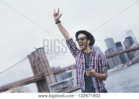 Man listening music with a rock sign hand up in Brooklyn, New York