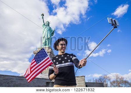 Tourist standing under the Statue of Liberty in New York with a selfie stick