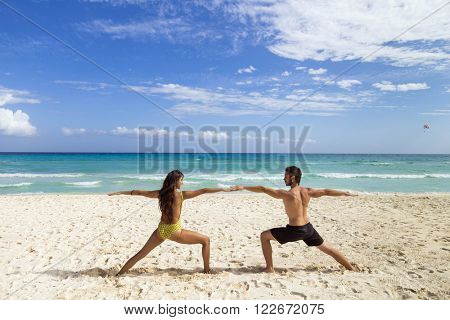 Couple practicing yoga together at the beach. Playa del Carmen, Mexico
