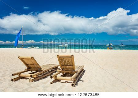 Tropical beach with chaise longues in foreground. Boracay island, Philippines