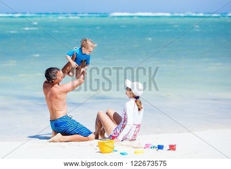Caucasian happy couple with little son having fun on the beach