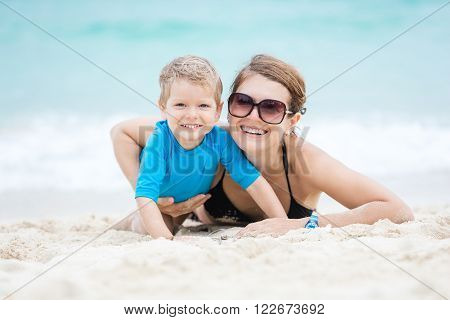 Young woman and her son having fun on the beach