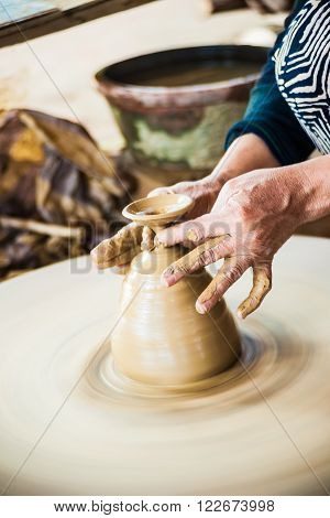 Closeup view of hands of a senior asian potter forming clay into a pot on a turntable. Image of asian handcrafts and manuafacture.