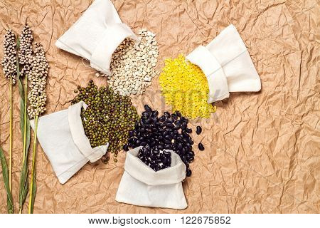 Type beans and lentils in sack on brown paper background millet mung bean soybean black bean