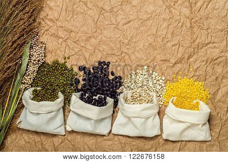Mixed beans in sack on brown paper background mung beansoybean black bean green beanmillet