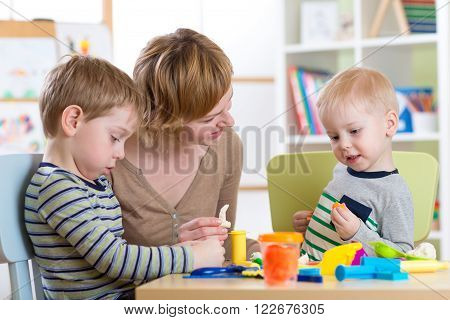 Kids playing with play clay at home or kindergarten or playschool. Woman teaches children handiwork.