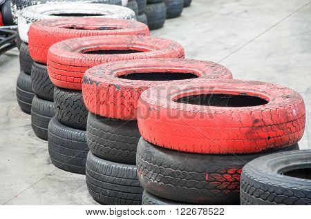 Stacked blacked tires topped with colourful red and white tires on a concrete surface.