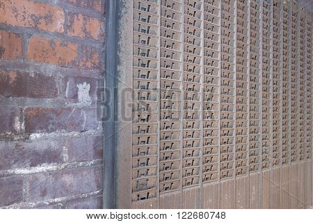 Rusted metal timecard holder on aging brick wall.