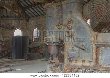 Antique blacksmithing tools inside brick steel mill.