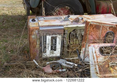 Abandoned antique fuel pump being overgrown with weeds on ground next to truck in field.