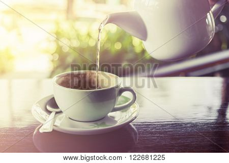 Cup of coffee with water splashing from hot pot on wooden and blur background Vintage style Selective focus