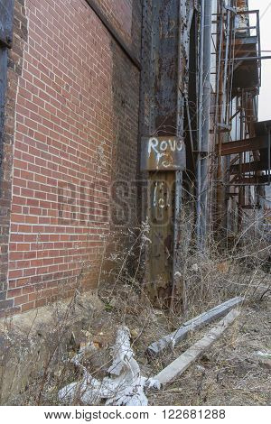 Alley between brick buildings of old steel mill overgrown with weeds.