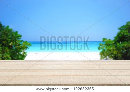 Beige wood table top panel on beautiful beach sea and sky blurred background use for display or montage products for advertisement in summer holiday concept