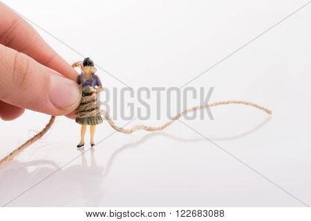 Woman figure in hand tied with a linen thread on a white background